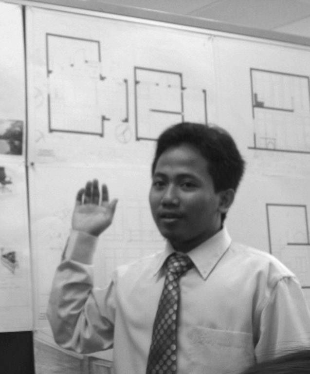 Muhamad Azizi Bin Hamzah stands in front of a floor plan drawing. He is dressed in a long sleeved shirt and tie.
