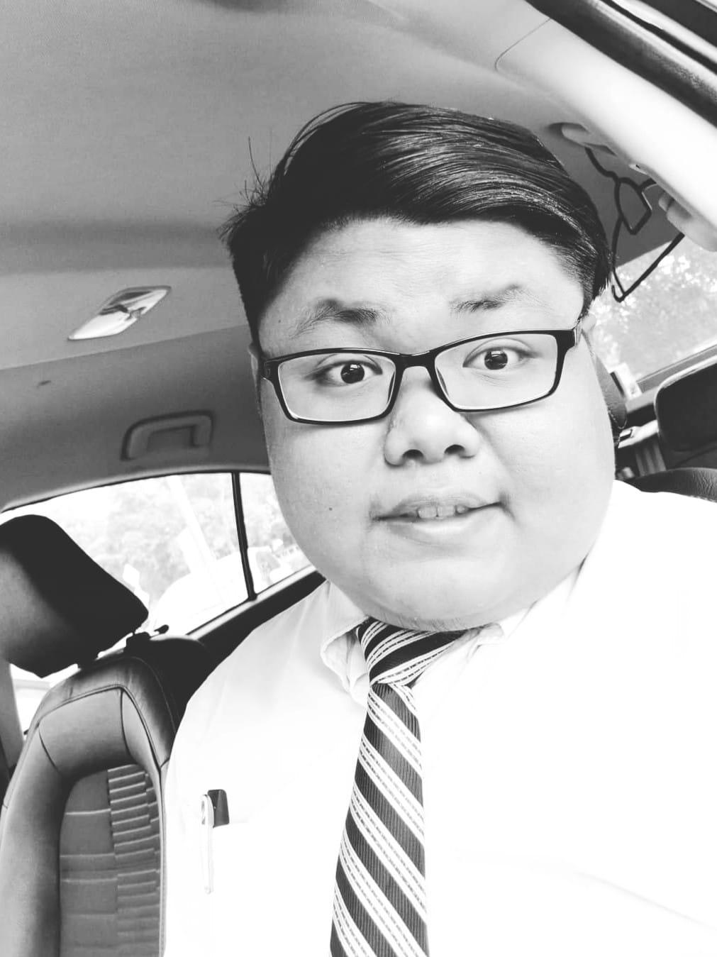 Zulhelmie Firdaus memakai kemeja dan bertali leher, gambar selfie di dalam kereta.