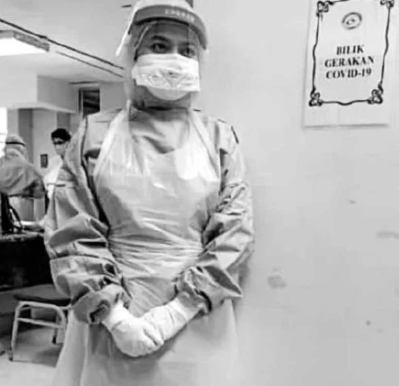 Siti Aishah Mohd Zamri, 26 - a young woman wearing full personal protective equipment, standing in front of a wall with the sign 'Bilik Gerakan Covid-19'.