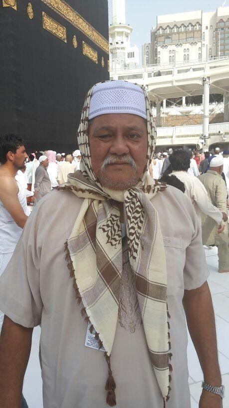 Amran Adam memakai jubah dan serban, dengan latar belakang Kaabah.