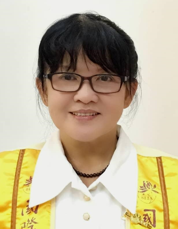 Su Ai Lian. A woman with a long fringe and dark rimmed rectangular glasses. She is smiling. She wears a bead necklace and a white collared blouse.