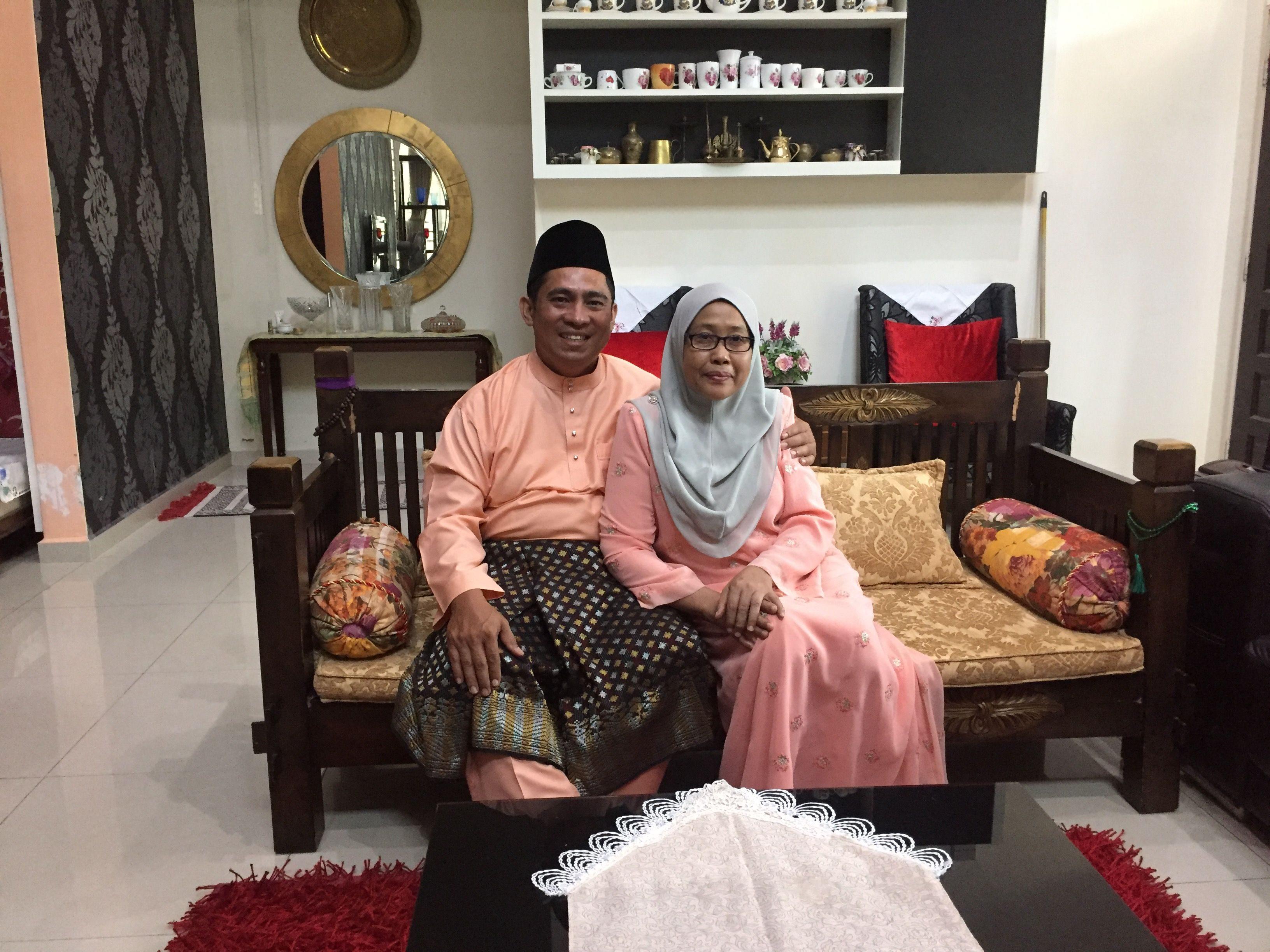 Nordin Ali duduk di atas sofa memeluk isterinya di sebelah. Keduanya memakai baju melayu dan tersenyum lebar