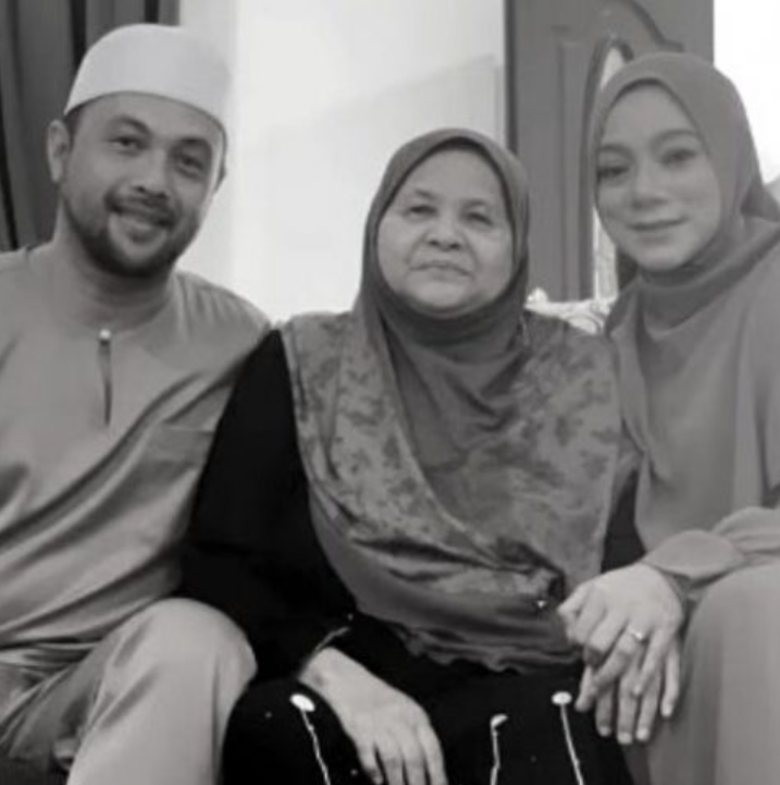 Tuan Zainab Syed Mamat seated in between her son and daughter-in-law. She wears a headscarf and a black long dress.