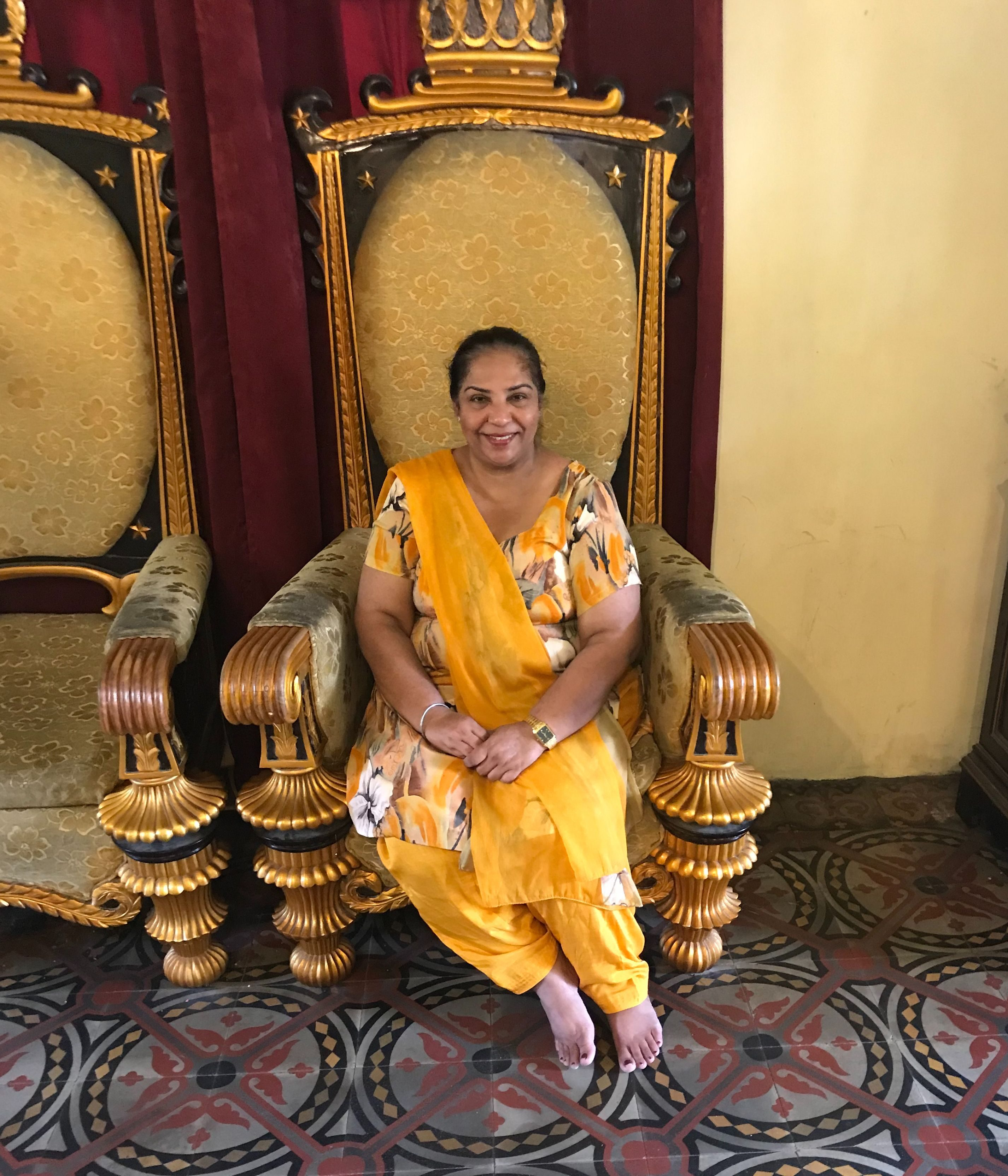 Harjit poses with a smile in her beautiful orange saree while sitting on a throne - like chair