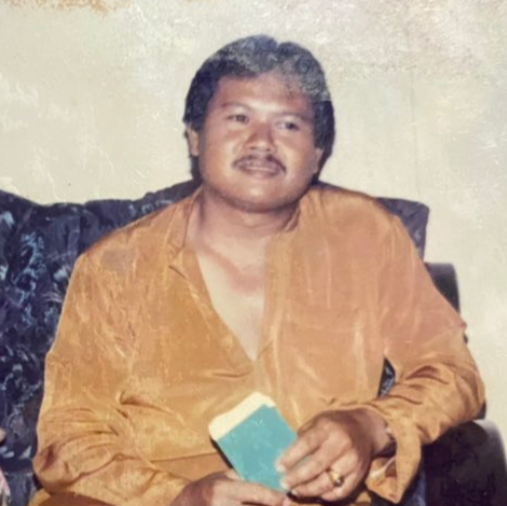Mohd Yusuf Jailan in unbuttoned yellow baju Melayu lounging and holding money packets.