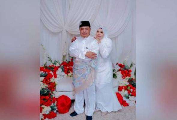 Safri and his wife embracing in one of their wedding pictures