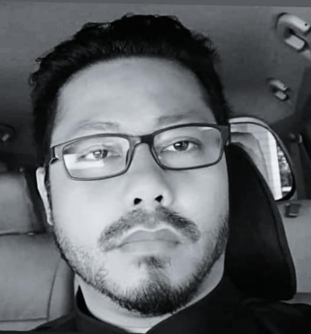 Hamzah Harun takes a pensive selfie. He has thick dark hair, a mustache and a goatee. He wears dark-rimmed glasses.
