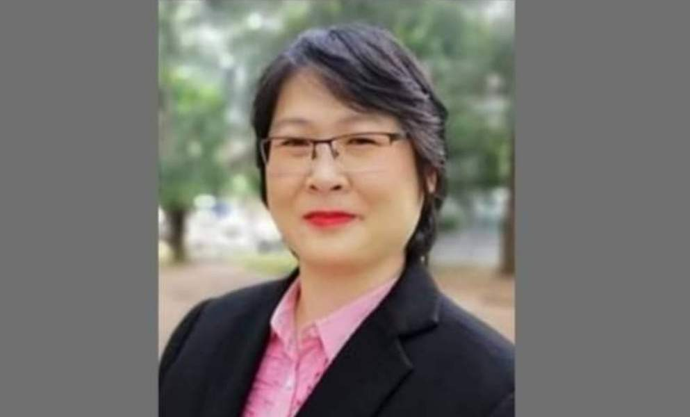 A professional portrait of Corrina Voon Ling Ling. She is a middle-aged woman with short hair and glasses. She is wearing a shirt and blazer.