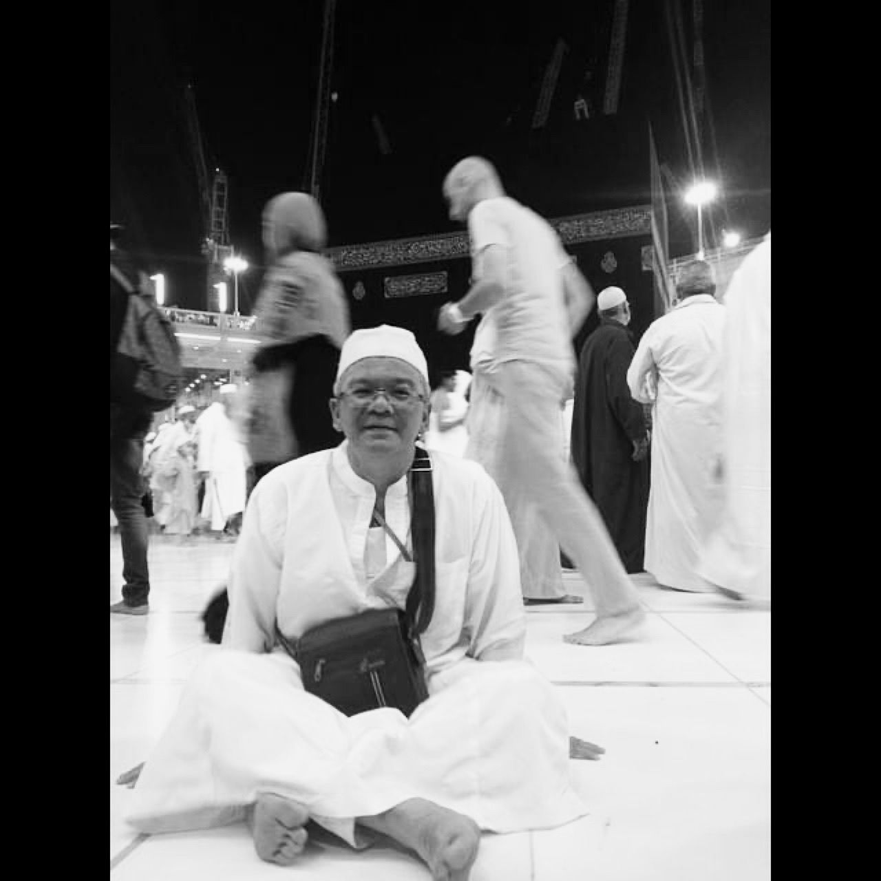 Raduwan Mohd Sharif tersenyum, duduk bersila, memakai beg sandang dengan latar belakang Kaabah.