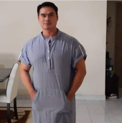 Abd Ghani Abu Hassan standing with his hands in the pockets of his short sleeved jubah (robe).