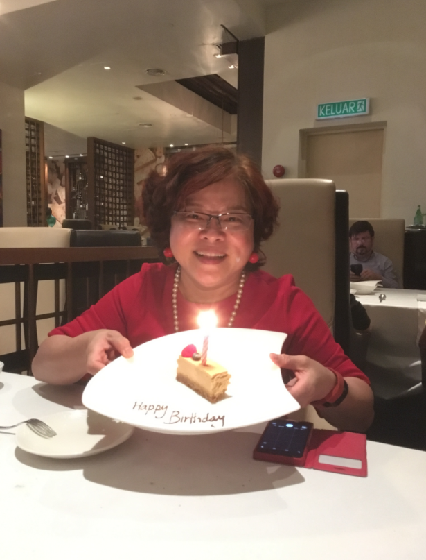 Fiona Wong smiles in front of her birthday cake, in a restaurant. She has short hair dyed red.