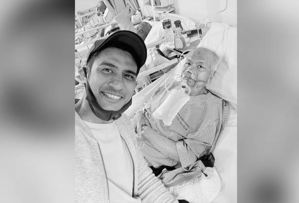 Muslim Bulat lies in a hospital bed, and receives oxygen supply. He is with his son, Ashraf.