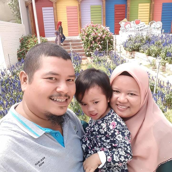 Nur Habibah bt Abdullah pose in front of a flower garden in Cameron Highlands, with her husband and young daughter.