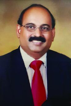Velu Kumar A/L Suppan in smiles in formal portrait, wearing a suit and tie. He has thinning hair and a bushy mustache.