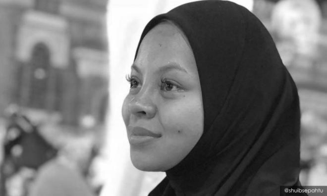 Siti Sarah Raisuddin wears a black headscarf and looks into the distance.