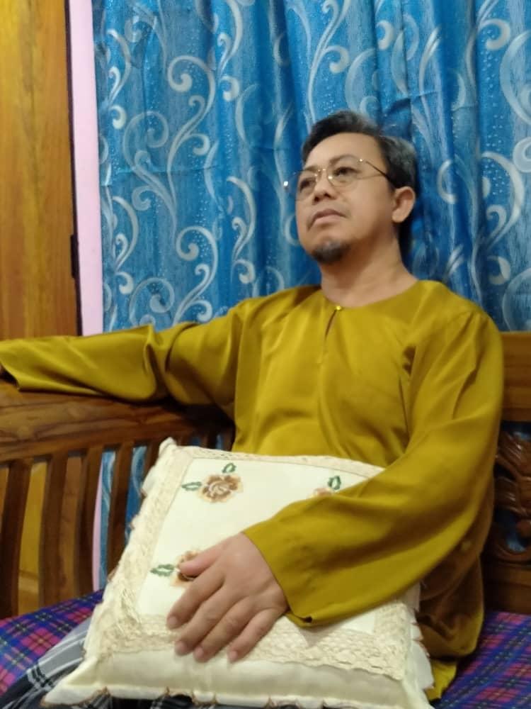 Johar bin Samat sits on a wooden chair. He has greying hair and a goatee. He wears rimless glasses and a baju melayu.