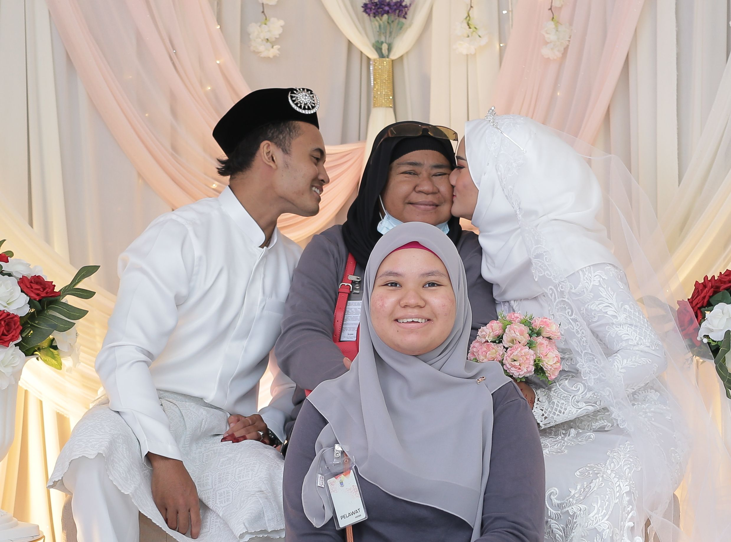 Robiah Binti Mat received a kiss from her daughter, on her daughter's wedding day.