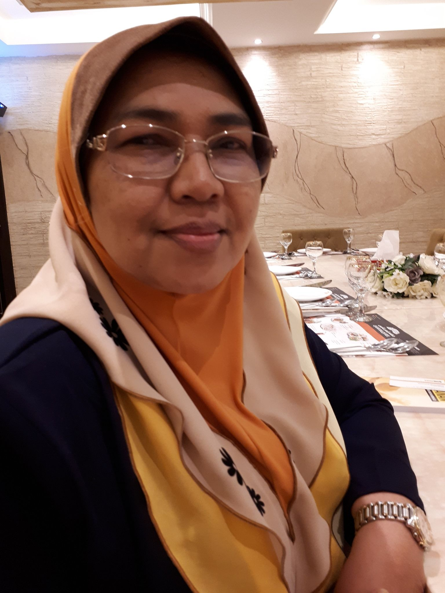 Azizah Mohd Yusoff sits at a restaurant table. She is wearing a layered, ruffled headscarf and glasses.