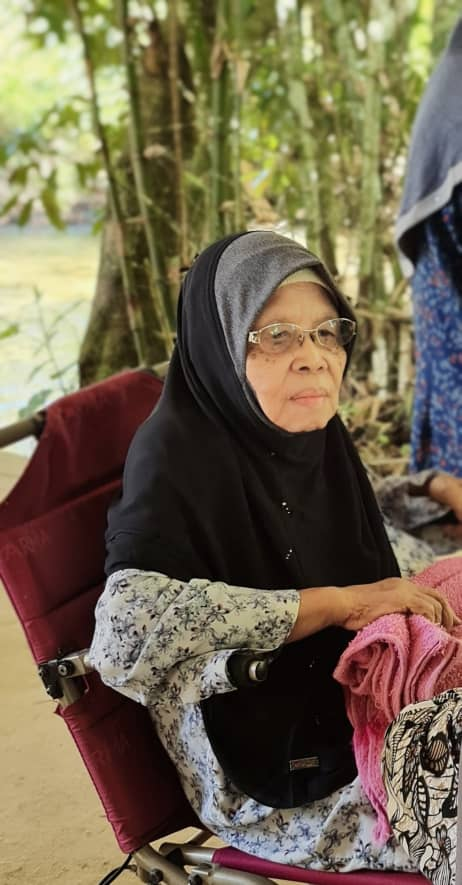 Hajjah Asiah binti Hassan sits on a chair during a picnic. She is wearing glasses, a black headscarf and a floral top. She is holding a red towel.