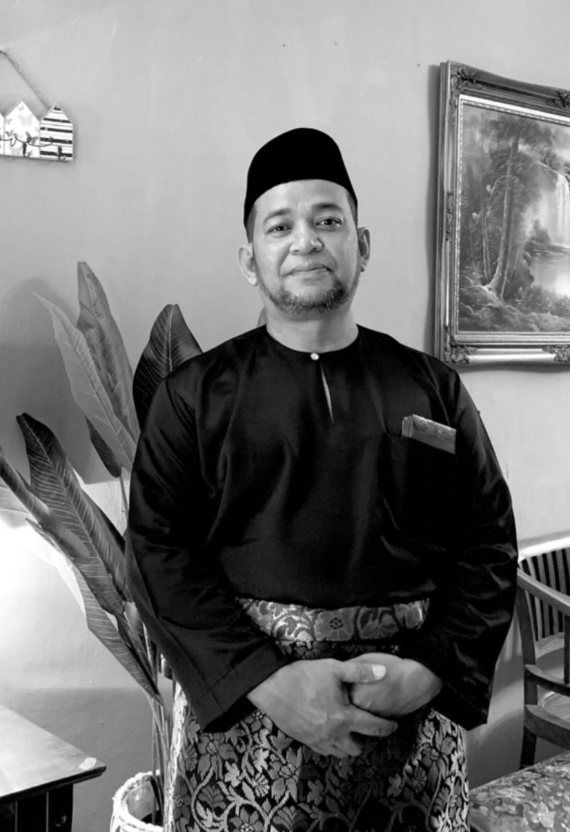Azhar Bin Saaid poses at home. He is wearing a songkok and baju melayu with sampin. He has a goatee and a youthful face.