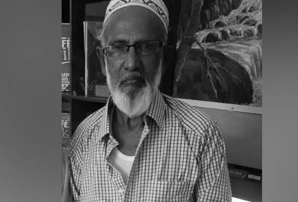 Jamal Mohamad Kadir Mydin, 85, wears a kopiah and a chequered shirt on top of a singlet. He has a white beard, a mustache and glasses.