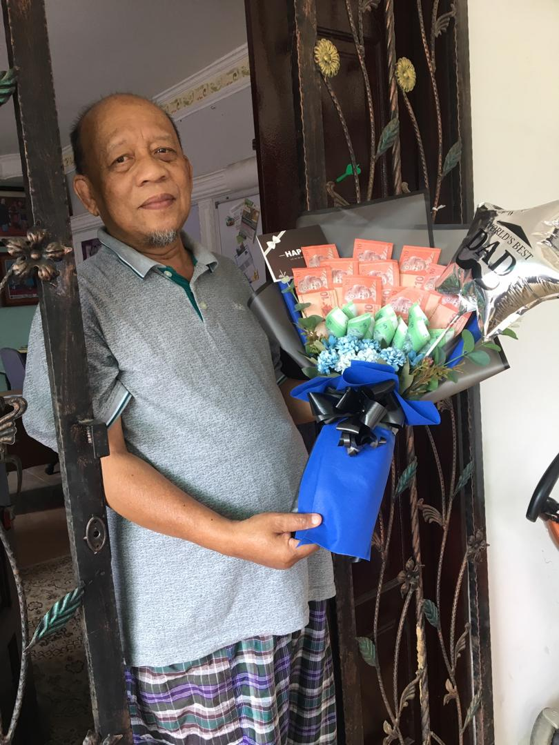 Jemali Marsidi, berdiri di pagar rumah dan tersenyum sambil memegang sejambak bunganga