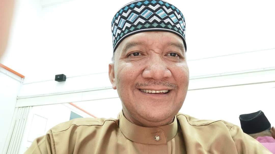 Abd Halim Bin Ahmad is smiling. He has a thin greying mustache. He wears a patterned kopiah and a baju melayu.