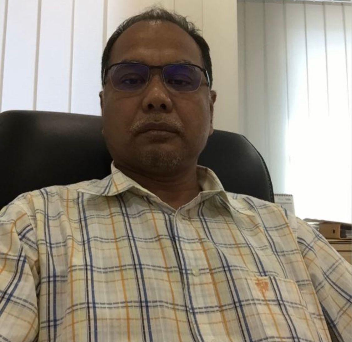 Mohd Yusri bin Ismail sitting in an office. He is wearing a chequered shirt.
