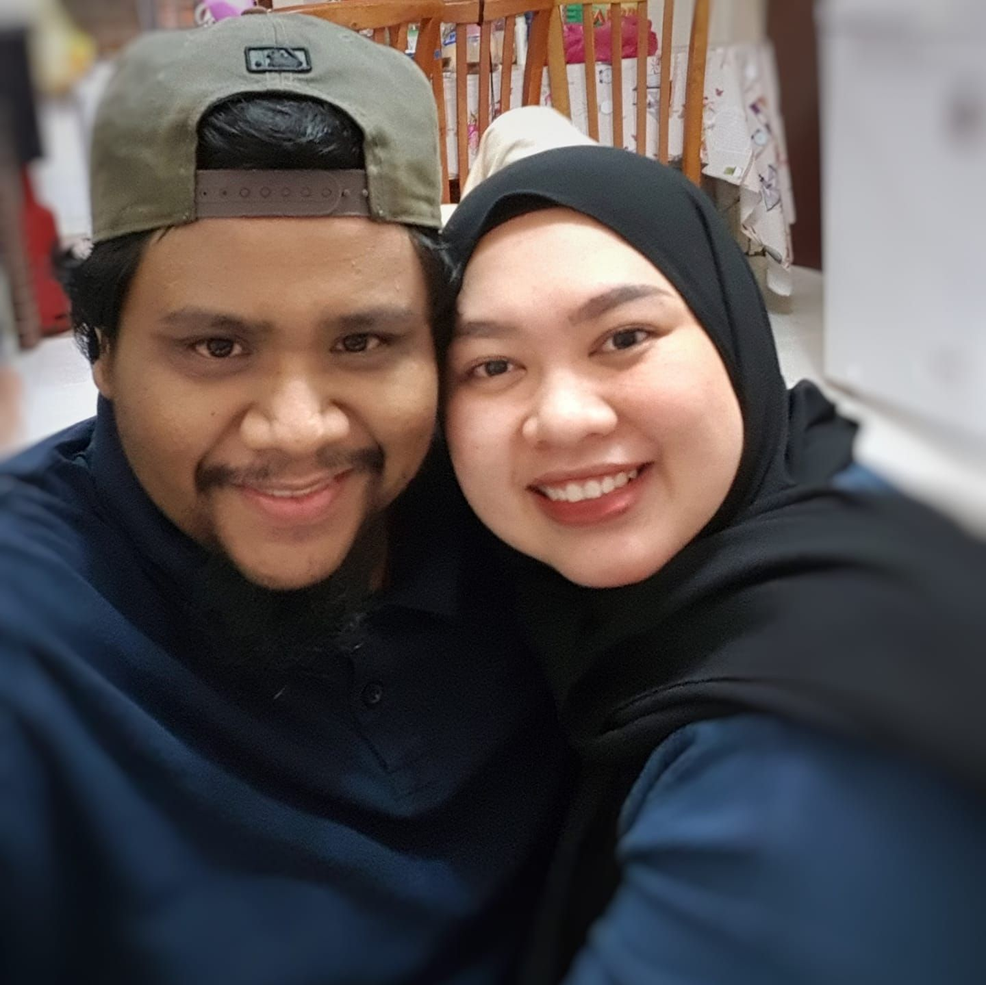 Muhammad Afiq bin Hamidi smiles in a wefie with his wife. He is wearing a cap backwards and has a mustache.