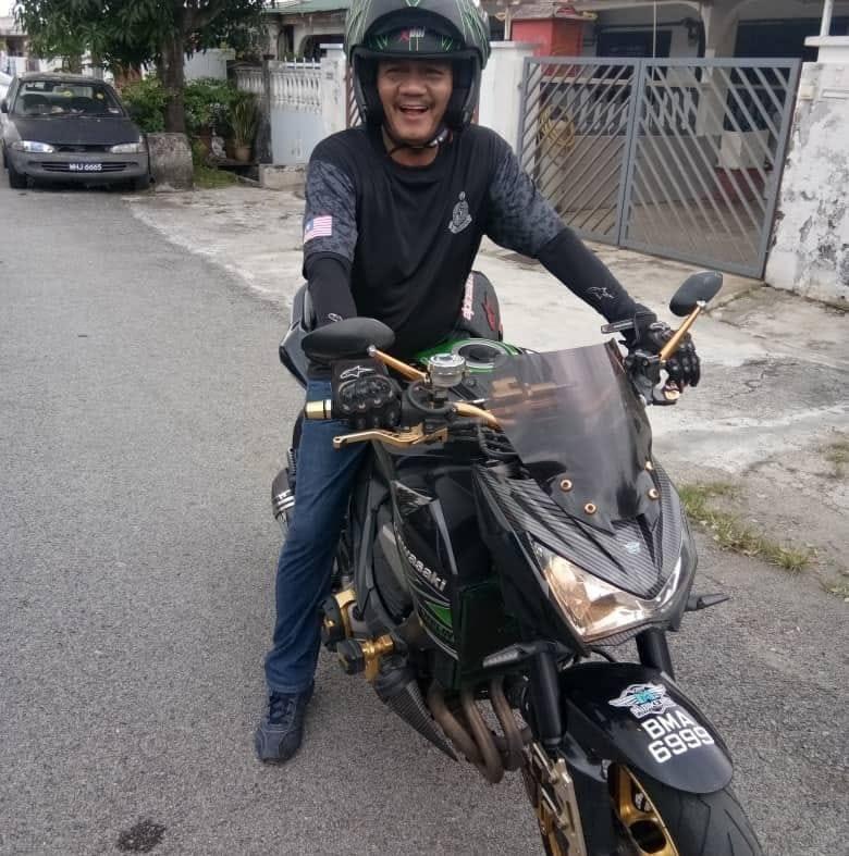 Zubir Bin Ahmad on smiles a motorcycle.