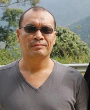 Mohd Azman bin Mohd Yatim has very short hair. He is wearing sunglasses and is wearing a V-neck T shirt.