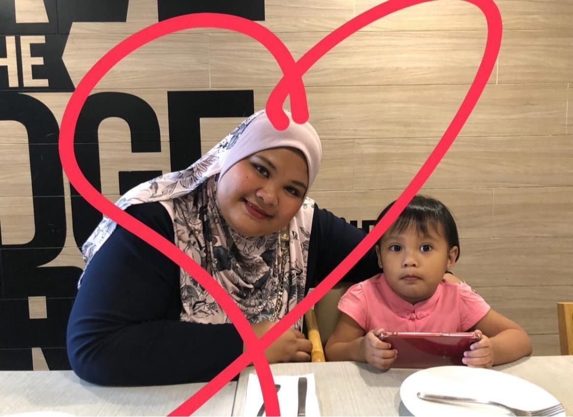 Wan Nur Amira Abd Shukor with her daughter. She is wearing a floral headscarf. A love heart is drawn around her.