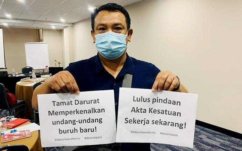 Badrulzaman Mohd Ghazali, in a face mask, holds up campaign placards urging for the end of the Emergency and pushing for labour law reforms.