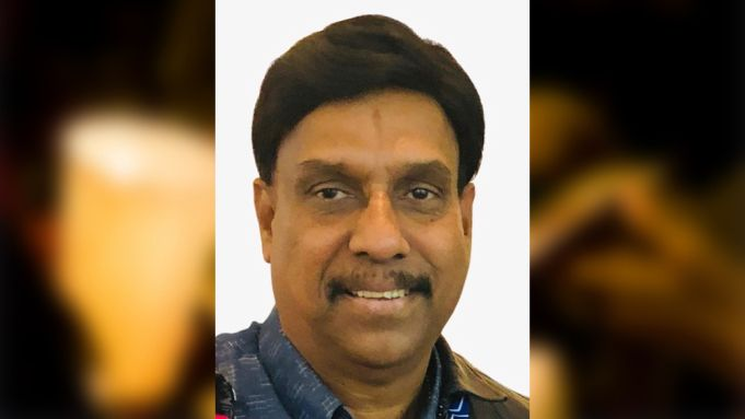 Balan Palanisamy, 64 -  a middle-aged man with tanned skin, thick black hair, a mustache and a prominent nose. He is smiling.