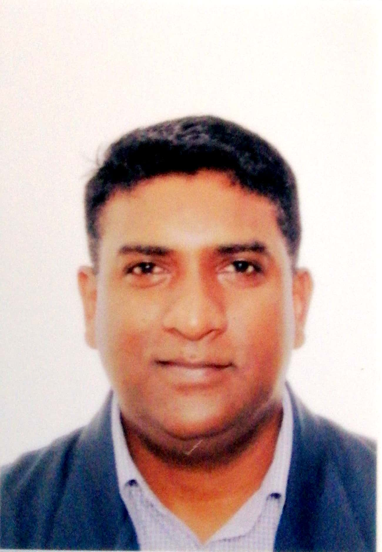 Mahendran Thevar smiles in a passport photo. He has thick hair and a round face.