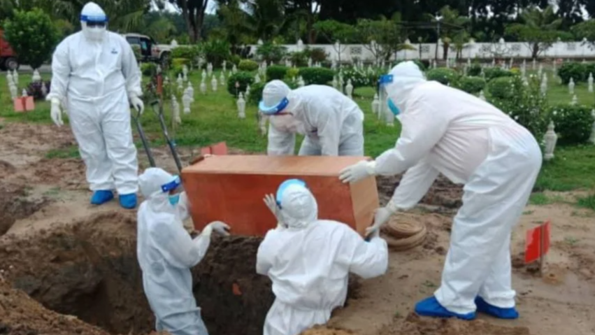 Medical officers clad in Personal Protective Equipment lowers Haikal's body into his final resting place