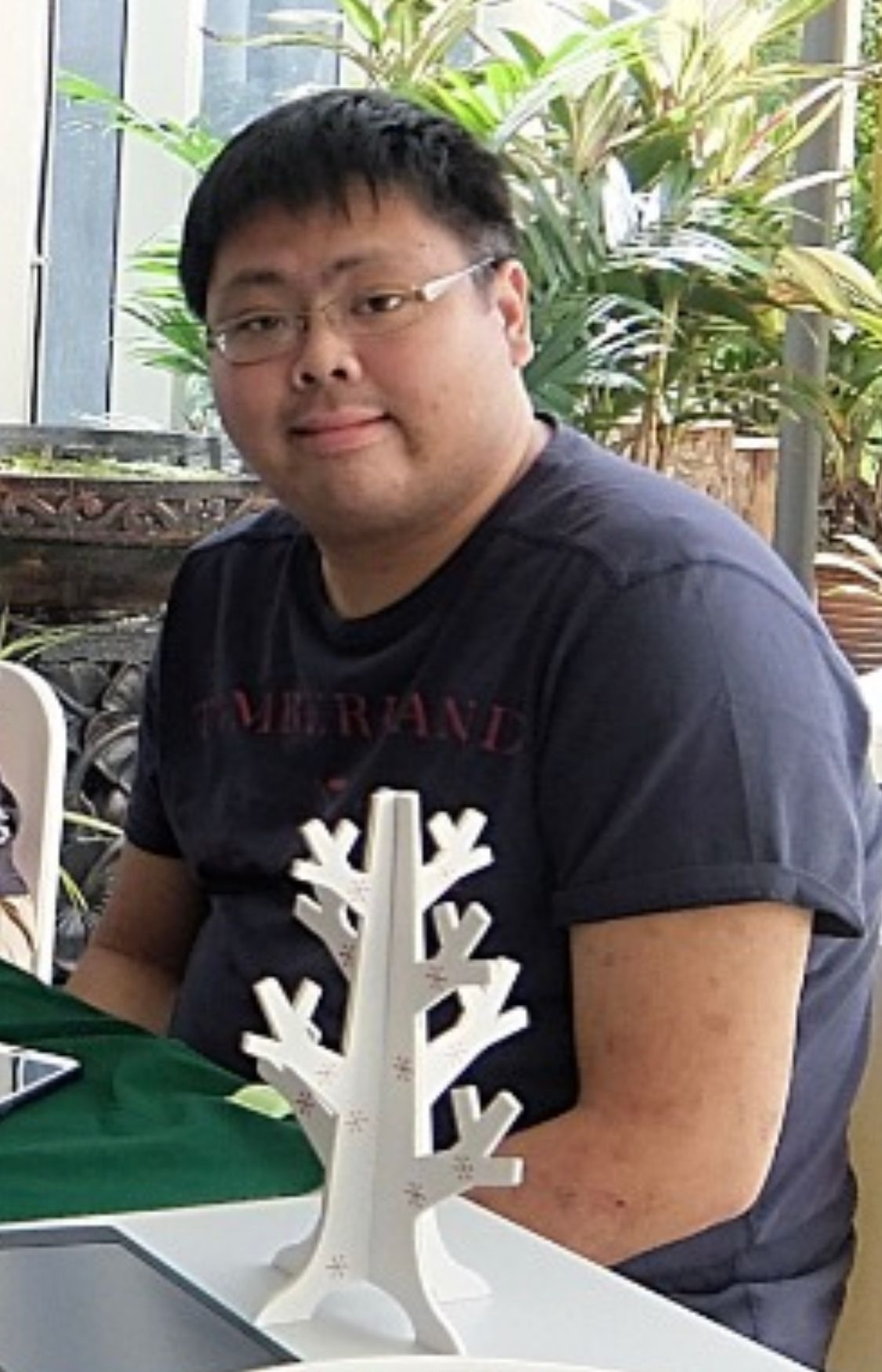 James, in short black hair, spectacles and a black T-shirt, sits at a table.
