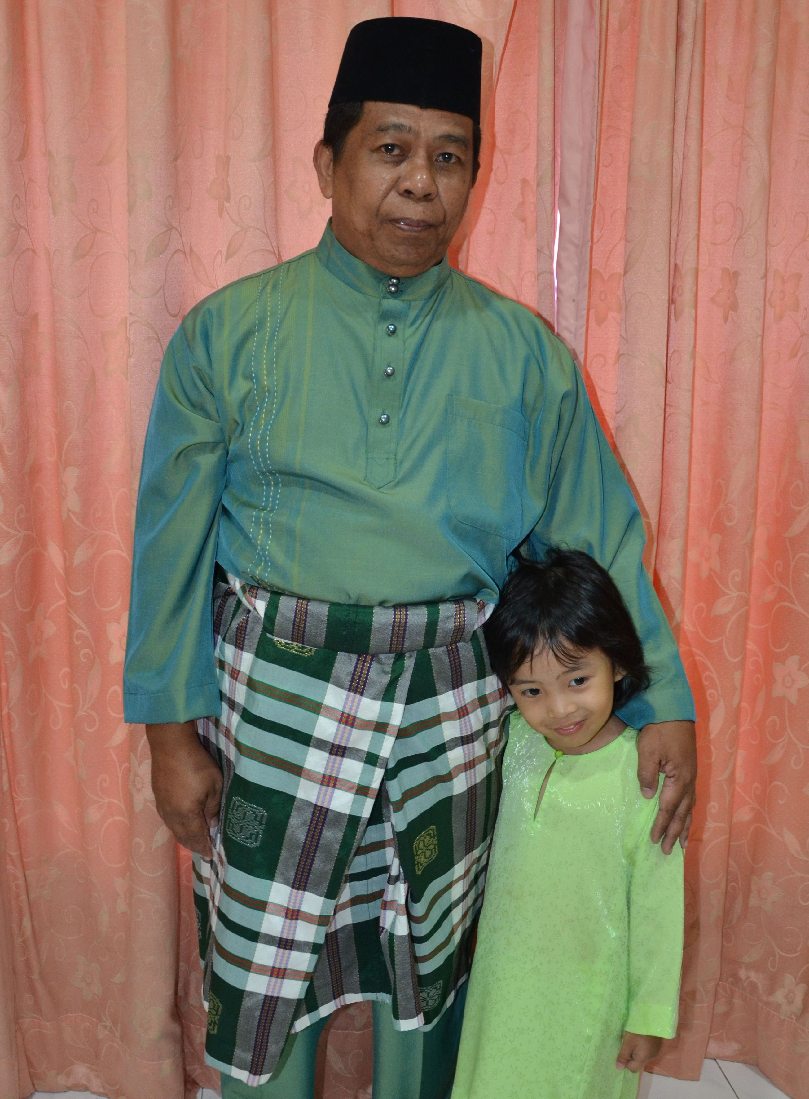 Abd Ghani poses with a smile in a green baju melayu with his hands lovingly wrapped around a child