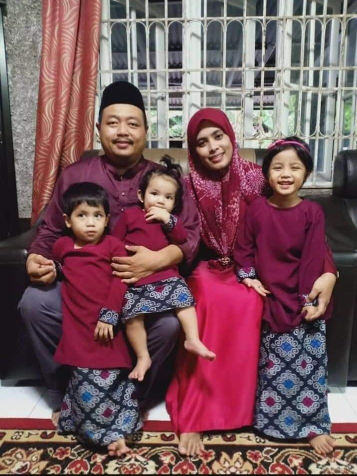 Mohd Sharizal Othman sits next to his wife. He has a daughter on his lap and a son in his arms. His wife has her arm around another daughter.