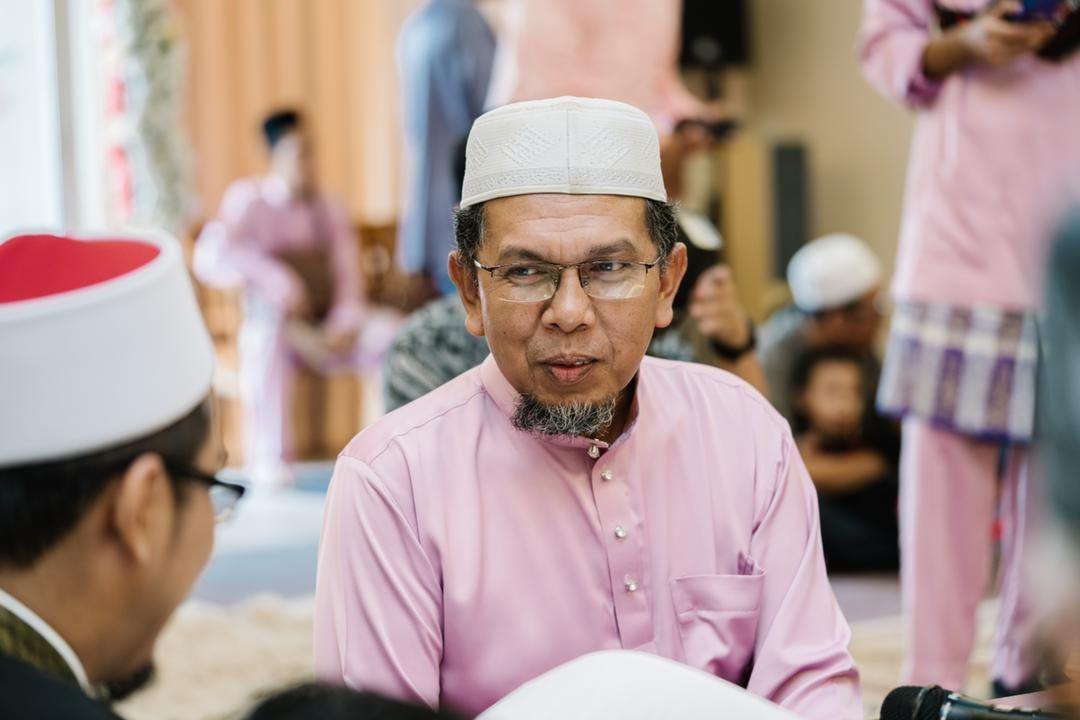 Abd Aziz Mat Said donning a pink baju Melayu photographed talking to another man