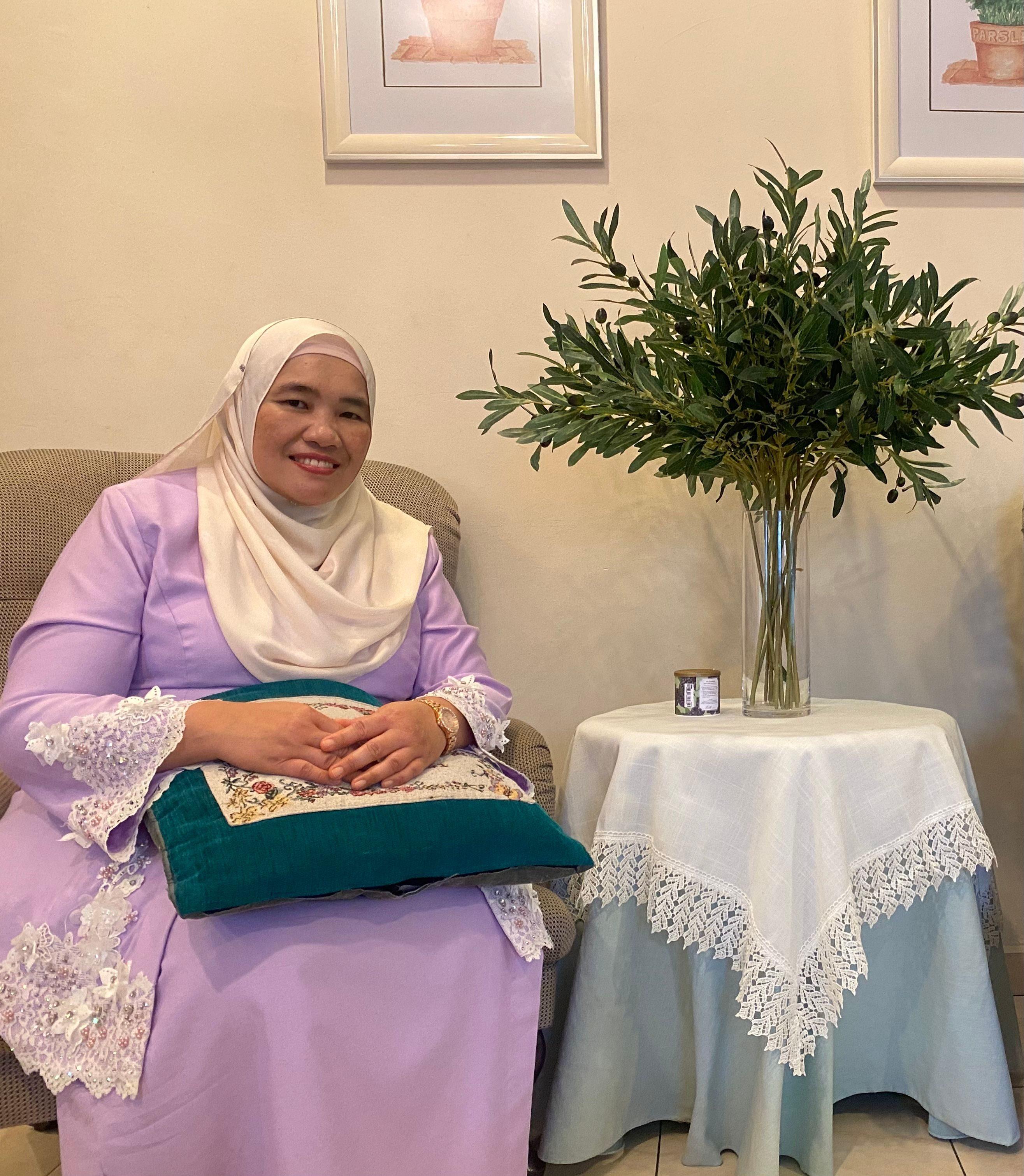 Mariam Binti Abd Jalal poses at home. She is smiling in a purple baju kurung. It is Hari Raya Aidilfitri.