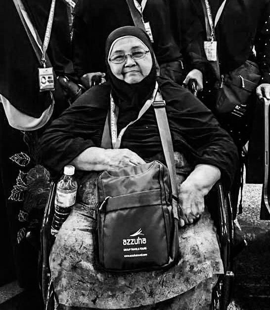 Jeriah Menit duduk di atas kerusi roda, menggalas beg sandang di hadapan, bercermin mata dan tersenyum.