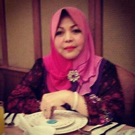 Hasimah at a dinner in a beautiful pink and black dress and purple hijab