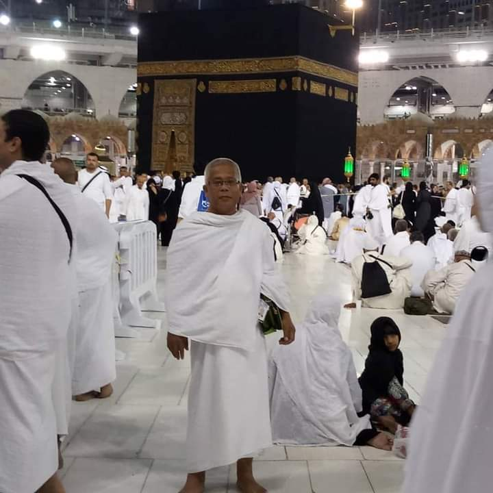 Ruzee bin Ramli poses in front of the Kaabah during his umrah. He is wearing the ihram.