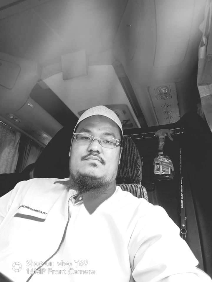 Mohammad Hafizuddin Abdul Halim takes a selfie in the driver's seat. He wears a kopiah, glasses and sports a goatee.