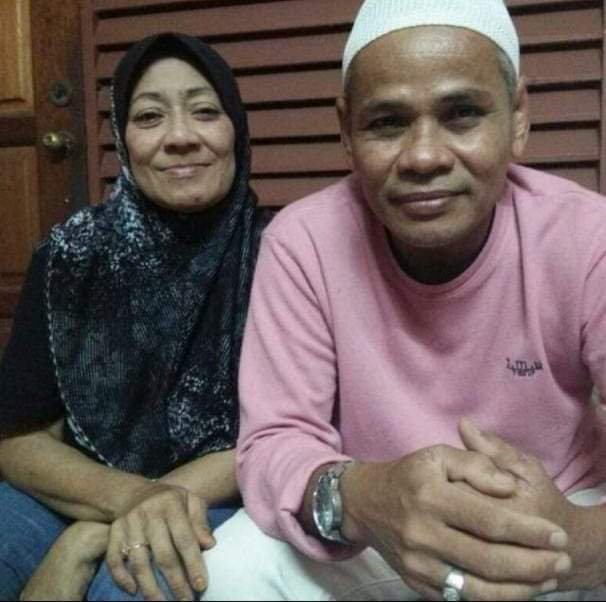 Mohamed Fadzil bin Zakaria sits next to an identified woman. He is wearing a kopiah and a pink long-sleeved T shirt. He is clean shaven and has a youthful face.