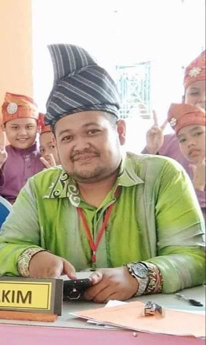 Mohd Zulkarnain Bin Hanipah as a judge at a dikir barat competition. He is wearing a tanjak and a batik shirt.