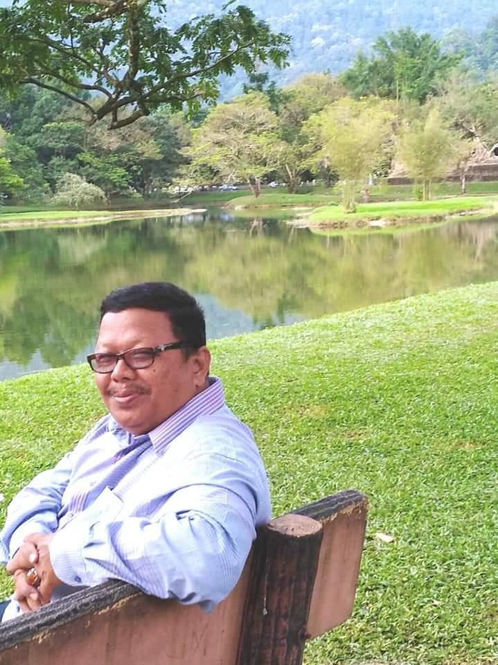 Mohd Yusoff memakai baju kemeja berwarna putih dan memakai cermin mata. Beliau duduk di atas bangku dengan latar belakang tasik.