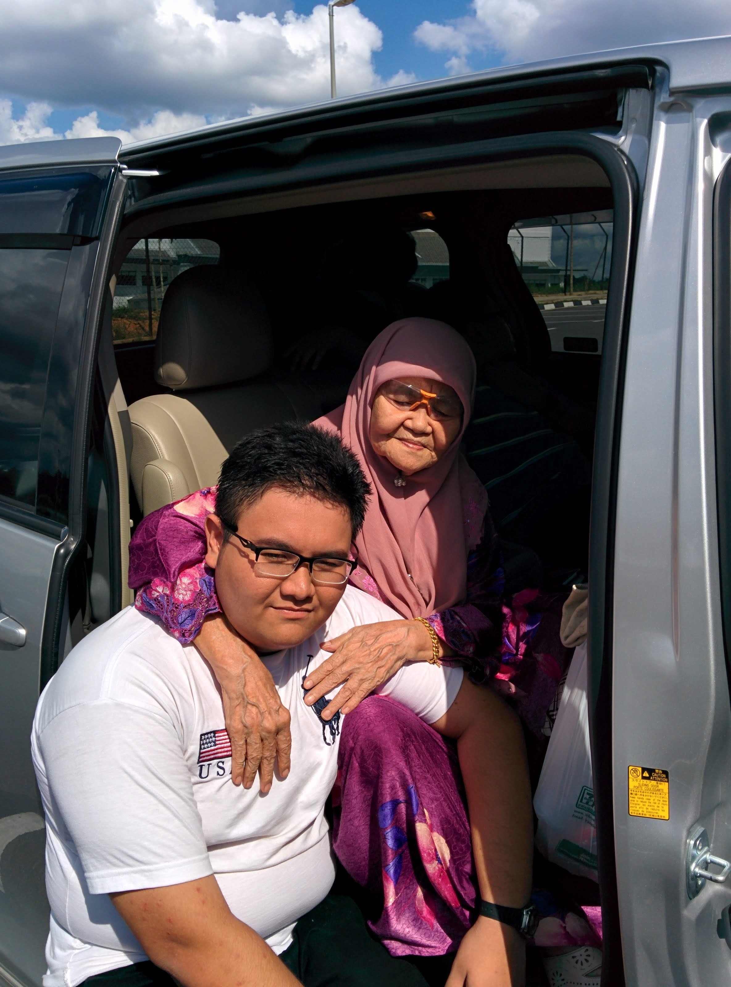 Ton binti Abdullah, 86, in a pink headscarf sits in a van and has her arms around a young man, believed to be her grandson.