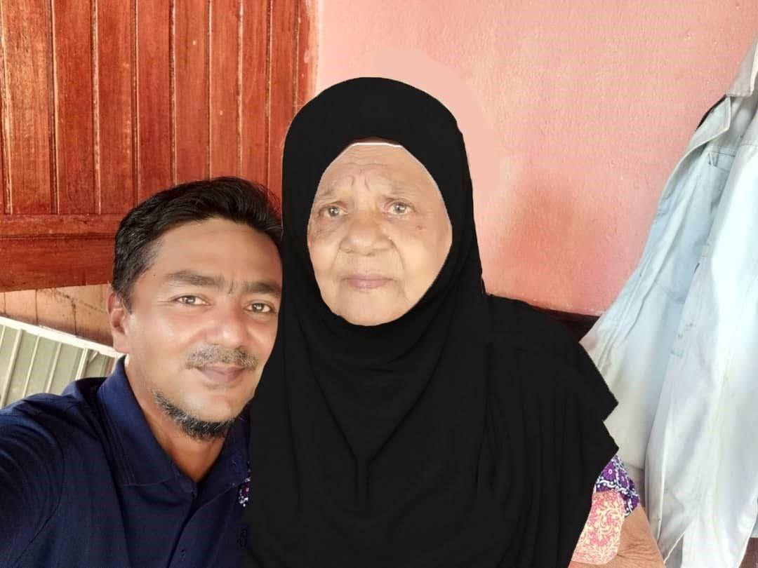 Hajah Alijah Binti Nabijanwith her son Rahmat Abd Rahman. She is wearing a headscarf.